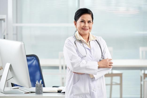 Huisarts staande armen gevouwen in het medische kantoor Gratis Foto