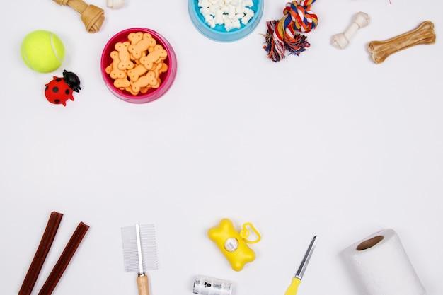 Huisdierentoebehoren, voedsel en stuk speelgoed op witte achtergrond Premium Foto