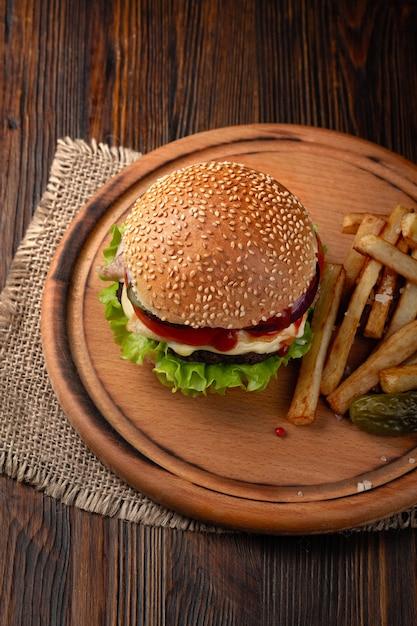 Huisgemaakt hamburgerclose-up met rundvlees, tomaat, sla, kaas en frieten op scherpe raad Premium Foto