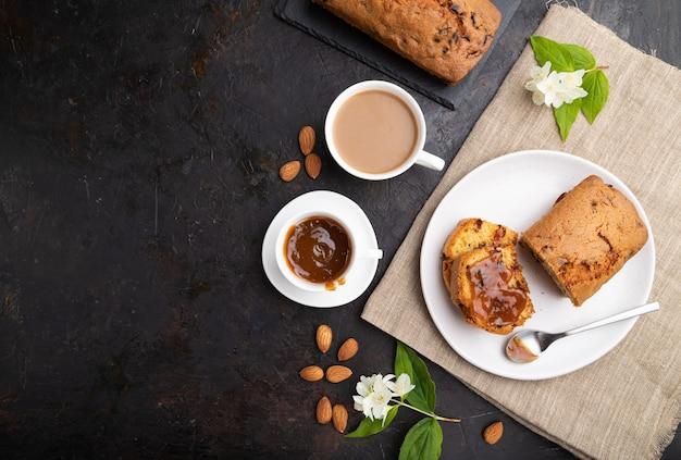 Huisgemaakte cake met rozijnen, amandelen, zachte karamel en een kopje koffie Premium Foto