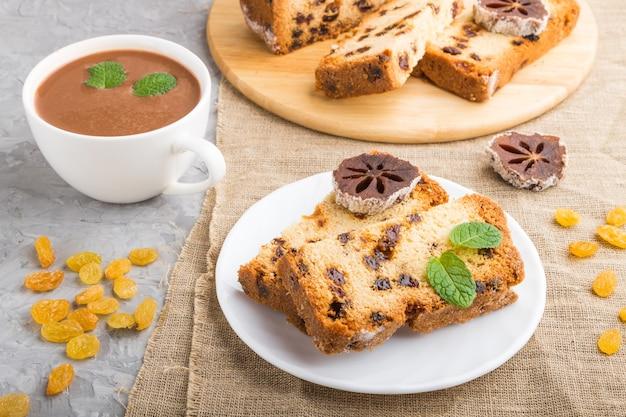 Huisgemaakte cake met rozijnen, gedroogde persimmon en een kop warme chocolademelk Premium Foto