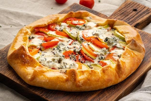 Huisgemaakte hartige galette met groenten, tarwetaart met tomaten, courgette, blauwe kaas gorgonzola. rustieke korstcrostata op donker linnen textieltafelkleed. Premium Foto