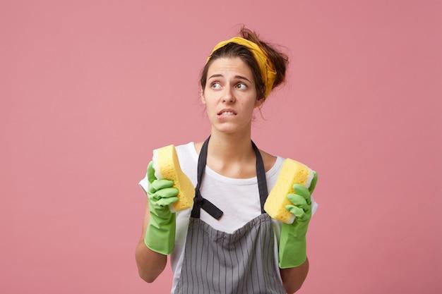 Huishouding, huishoudelijk werk, hygiëne en netheid. gefrustreerde jonge vrouw in schort en beschermende handschoenen die op haar lip bijten, zich gestrest voelen omdat ze de kamers niet haalt voordat de gasten komen Gratis Foto