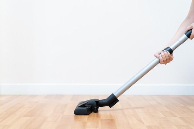 Huishoudster die vacuümmachine schone houten vloer in het huis gebruiken. Premium Foto