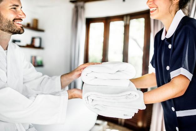Huishoudster die verse handdoeken overhandigt Premium Foto