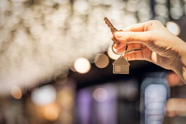 Huismodel en sleutel in makelaarskantoor Premium Foto