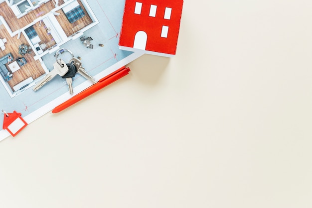 Huismodel en sleutels met blauwdruk op witte achtergrond wordt geïsoleerd die Gratis Foto