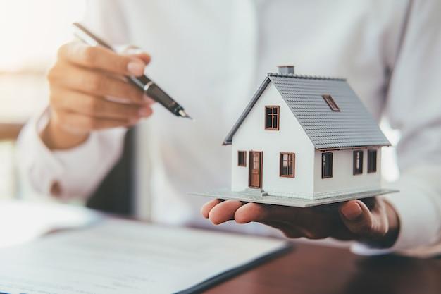 Huismodel met onroerende goederenagent en klant die voor contract bespreken om huis te kopen Premium Foto