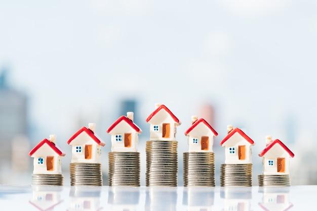Huismodellen bovenop muntstukkenstapel met stadsachtergronden. Premium Foto