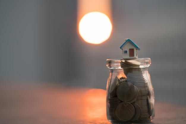 Huismodellen bovenop muntstukkruik met zonsondergangachtergronden. Premium Foto