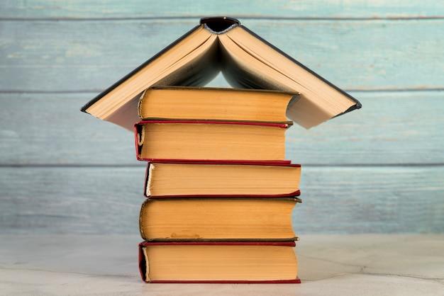 Huisstructuur met uitstekende boeken tegen houten muur wordt gemaakt die Gratis Foto