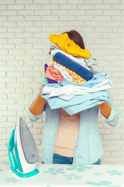 Huisvrouw die een enorme stapel wasgoed op de strijkplank brengt Premium Foto