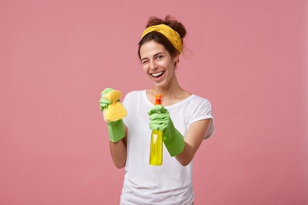 Huisvrouw in wit t-shirt en groene handschoenen met spons en reiniger in handen knipperend met haar ogen met blije uitdrukking tijdens het wassen. jonge mooie vrouw die huishoudelijk werk doet Gratis Foto