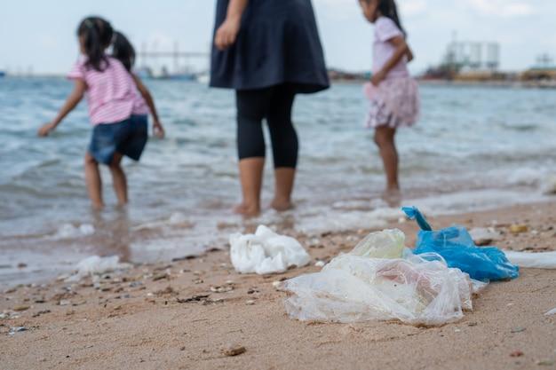 Huisvuil op het strand met familie speelwater in het overzees op achtergrond Premium Foto