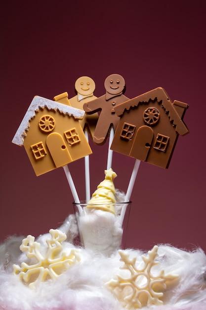 Huizen en mensen van zwarte en melkchocolade op een stokje Premium Foto