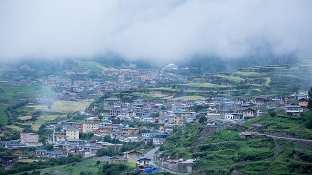 Huizen van een kleine stad omgeven door bossen en een mistige wolk Gratis Foto