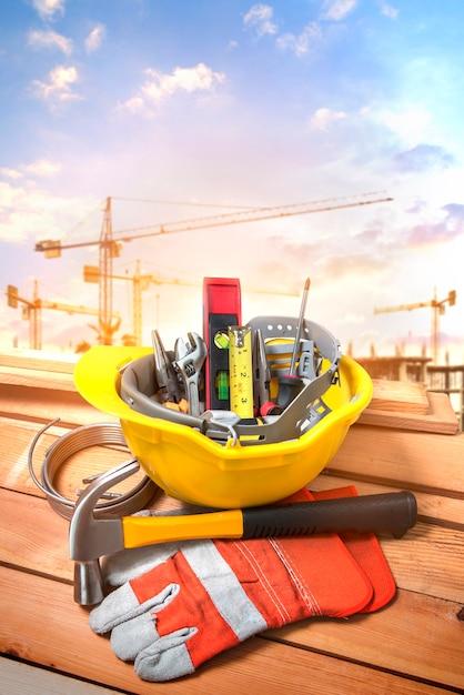 Hulpmiddelen in een gele helm op een bouwplaats met een achtergrondkraan. Premium Foto