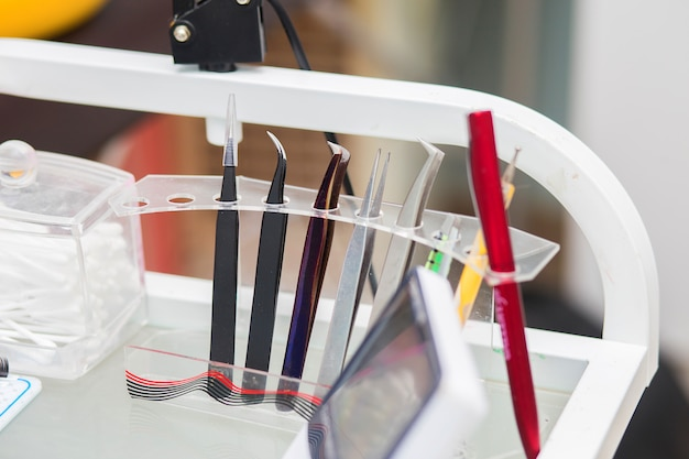 Hulpmiddelen van de meester in wimperuitbreidingssteun in een steun op een desktop, in schoonheidswinkel Premium Foto