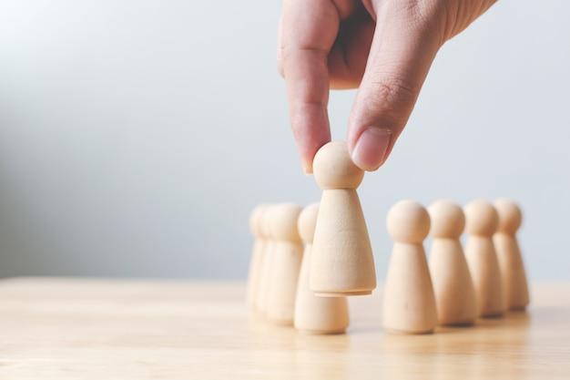 Human resources, talent management, recruitment employee, succesvol business teamleider concept. hand kiest een houten persoon die uit de menigte opduikt. Premium Foto