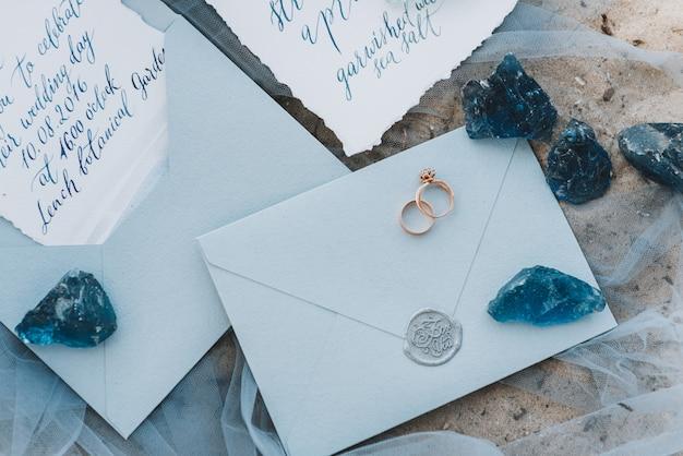 Huwelijk en verlovingsringen op een envelop naast uitnodiging en menu Premium Foto