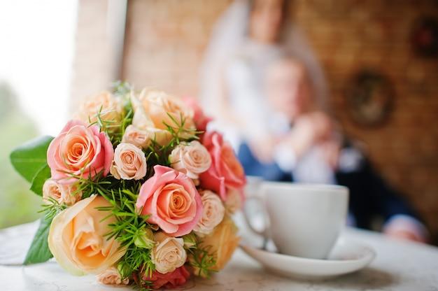 Huwelijksboeket bij uitstekende koffiejonggehuwde Premium Foto