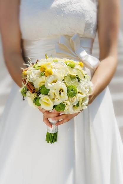 Huwelijksboeket in de handen van de bruid Premium Foto