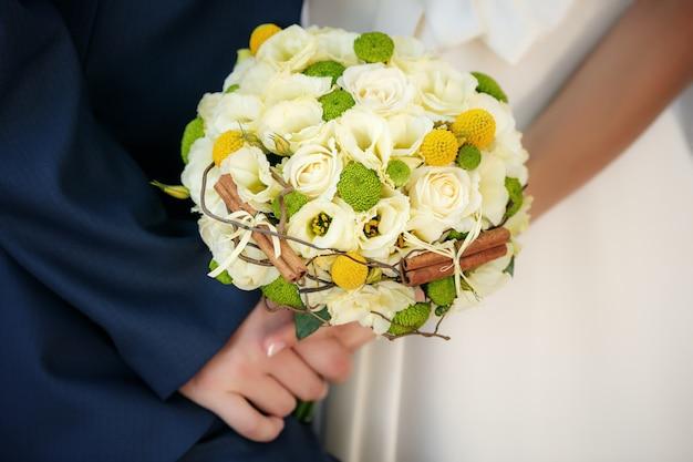 Huwelijksboeket in handen van de bruid en de bruidegom Premium Foto