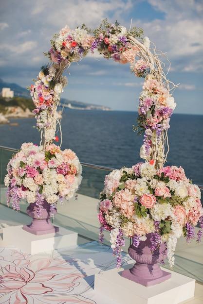 Huwelijksboog met verse bloemen op een zee achtergrond. vazen met verse bloemen. Premium Foto