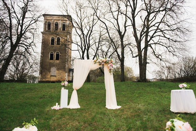 Huwelijksboog versierd met doek en bloemen buitenshuis. mooie bruiloft opgezet. huwelijksceremonie op groen gazon in de tuin. onderdeel van het feestelijke decor, bloemstuk. Premium Foto