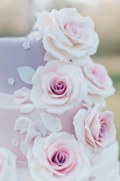 Huwelijkscake in pastelkleuren met realistische roze rozen op een vage achtergrond van de tuin worden verfraaid, selectieve nadruk die Premium Foto