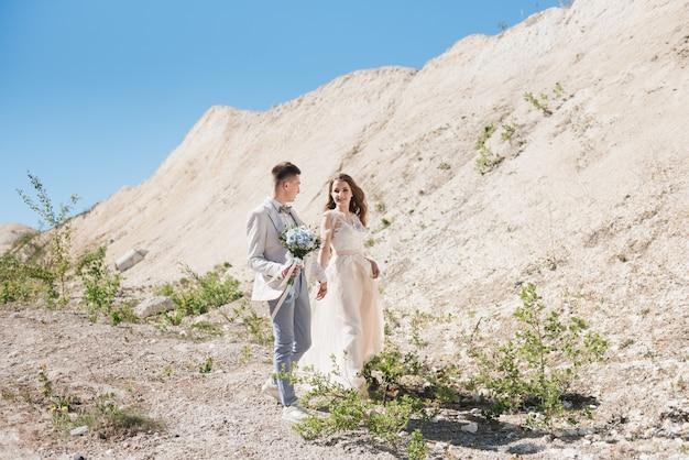 Huwelijksceremonie in de bergen. de bruid en bruidegom staan voor de zanderige bergen. het gelukkige paar, een prachtige bruiloft op een schilderachtige locatie Premium Foto