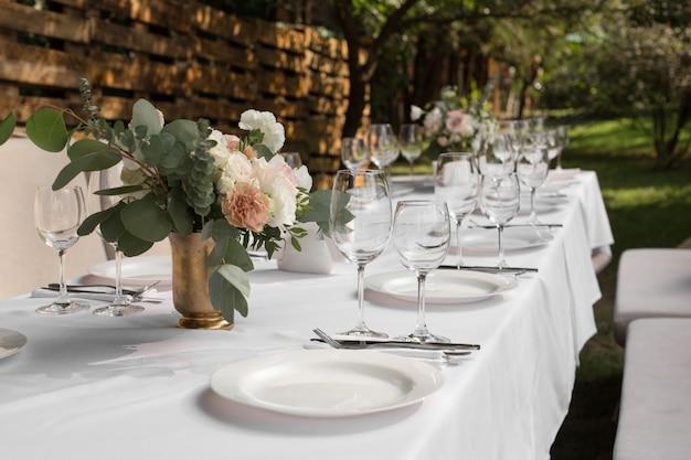 Huwelijkslijst die plaatsen die met verse bloemen in een messingsvaas wordt verfraaid Premium Foto