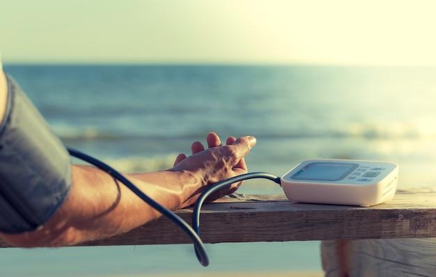 Hypertensieve patiënt die een automatische bloeddruktest op het strand uitvoert Premium Foto