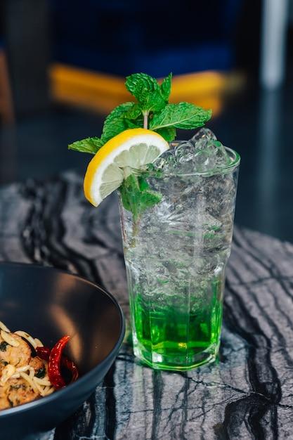Iced apple soda met gesneden citroen en muntblaadjes in drinkglas op marmeren boven tafel. Premium Foto