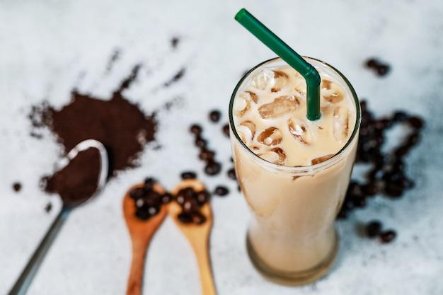 Iced latte verse koffie gezet op de stenen tafel met bonen en poeder koffie. fris drankje met goede grondstof voor een goede smaak. Premium Foto