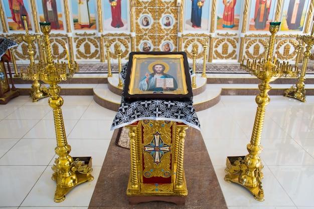 Icoon van jezus christus de almachtige op een vergulde standaard naast kandelaars Premium Foto