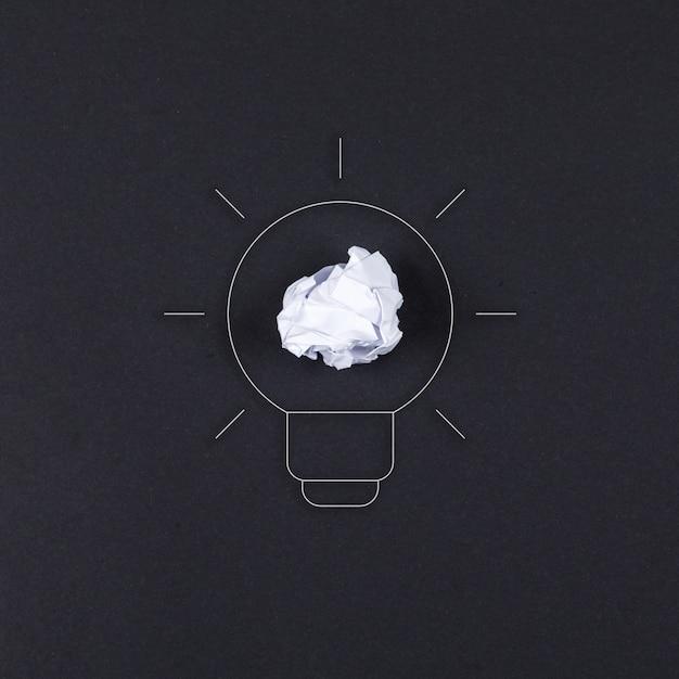 Ideeconcept met lamp, verpletterd document op zwarte hoogste mening als achtergrond. horizontaal beeld Gratis Foto