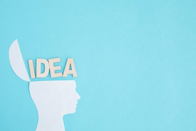 Ideetekst over het open hoofd op blauwe achtergrond Gratis Foto