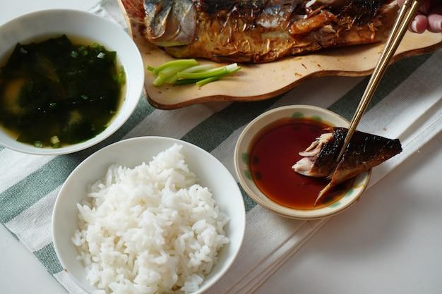 Iemand die eetstokjes gebruikt en een stuk gegrilde saba of makreelvis probeert te plukken en op zoete saus plakt, geserveerd met gekookte rijst en misosoep op witte en groen gestreepte placemat op witte tafel Premium Foto