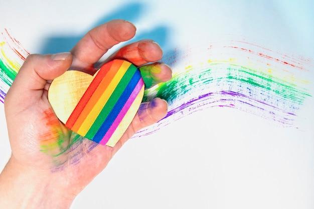 Iemands hand met een hart met lgbt-symbolen. getekende regenboog op de achtergrond. vrije liefde. lesbische homo biseksuele transgender. valentijnsdag. Premium Foto