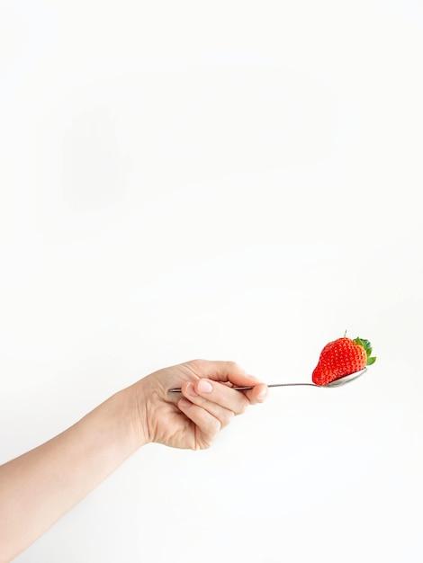 Iemands hand met een lepel met een aardbei op een wit oppervlak Gratis Foto