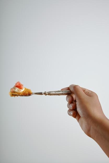 Iemands hand met een vork met een stukje heerlijke biscuit met grapefruit geïsoleerd op wit Gratis Foto