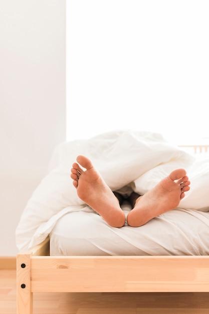 Iemands voeten onder deken Gratis Foto