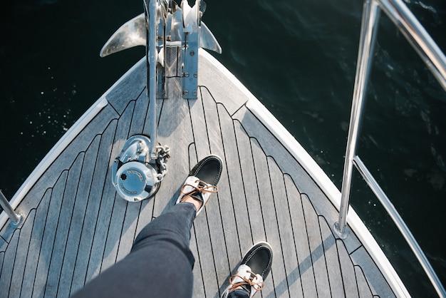 Iemands voeten op de boot die overdag op zee vaart Gratis Foto