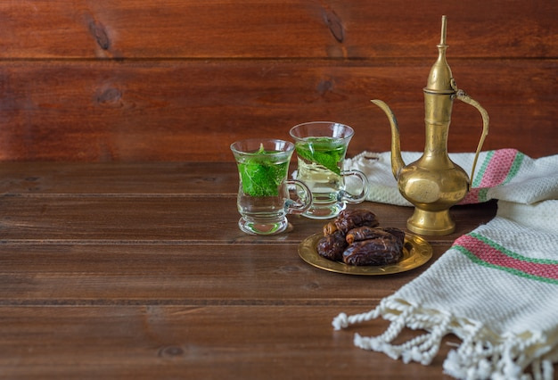 Iftar en suhoor ramadan-concept, mentha thee op glazen bekers en dadels Premium Foto