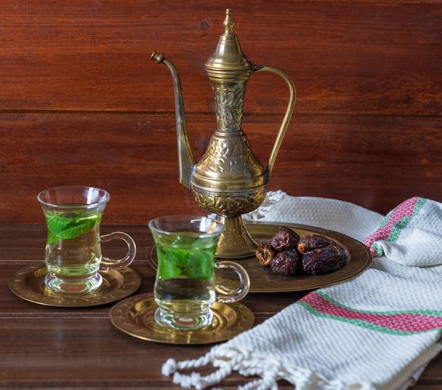Iftar en suhoor ramadan-concept, mentha thee op glazen kopjes en dadels met een oude theepot Premium Foto