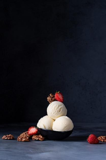 Ijs drie ballen met aardbeien en walnoten op een donkere achtergrond Premium Foto