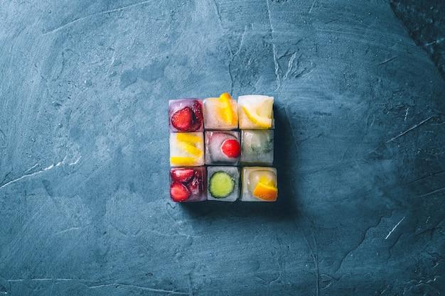 Ijsblokjes met fruit op een steen blauwe ondergrond. de vorm van het vierkant. munt, aardbei, kers, citroen, sinaasappel. plat lag, bovenaanzicht Premium Foto