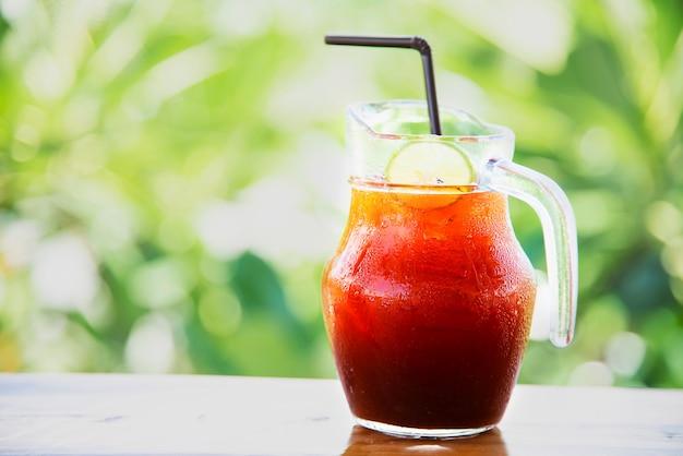 Ijsthee op houten lijst over groene tuin - ontspan met drank in aardconcept Gratis Foto