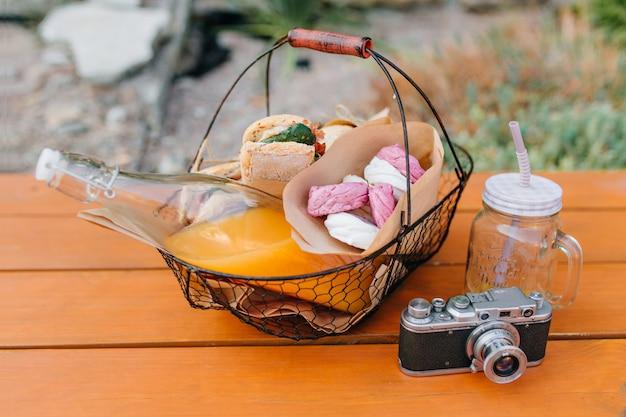 Ijzeren mand met fles jus d'orange en sandwiches staande op houten tafel. buitenfoto van maaltijd voor picknick, leeg glas en camera. Gratis Foto